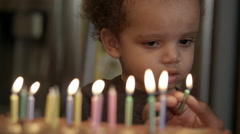 Young boy crys after he burns himself on birthday candle. His mother tries to Stock Footage