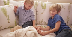Young blond boy tickling his brother's feet on a sofa Stock Footage