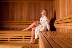 Beautiful woman sitting relaxed in a wooden sauna white coat - stock photo