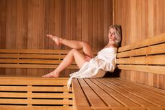 Beautiful woman sitting relaxed in a wooden sauna white coat Stock Photos