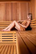 Beautiful woman sitting relaxed in a wooden sauna   brown towel - stock photo