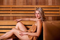 Beautiful woman sitting relaxed in a wooden sauna   brown towel Stock Photos