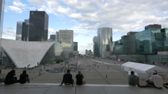 People taking pictures and sitting on the esplanade of La Défense, Paris Stock Footage