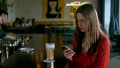 Young attractive Caucasian female using her phone in retro styled cafe - stock footage