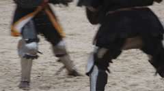 Two strong knights wearing steel armor fighting actively, medieval tournament Stock Footage