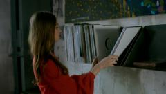 Young adult attractive Caucasian female looking through vinyl records Stock Footage