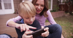 Closeup of handsome young boy looking at cellphone with mom Stock Footage