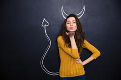 Cute woman with devils horns and tail drawn on blackboard - stock photo