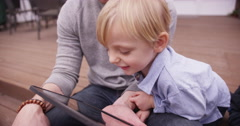 Close-up of cute white boy looking at handheld tablet device - stock footage