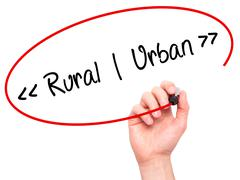 Man Hand writing Rural - Urban with black marker on visual screen. Stock Photos