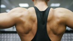 Muscular back of a body builder as he trains, in slow motion Stock Footage