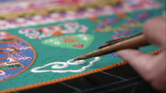 Tight shot of someone adding white sand to a colorful sand mandala. - stock footage