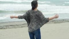 Happy excited woman turning round on the beach on a stormy day - stock footage