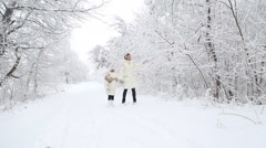 Mother and child walking  in the winter woods Stock Footage