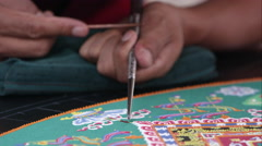 Tight shot of a man carefully adding sand to a symbolic sand mandala. Stock Footage
