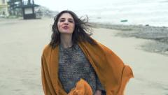Portrait of young, happy woman walking on beach during stormy day, super slow Stock Footage