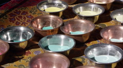 Panning shot of many bowls of colored sand for making sand mandalas. Stock Footage