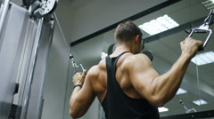Young man using a cable pulley machine in the gym Stock Footage