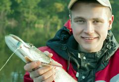 Portrait of a young fisherman with pike Stock Photos