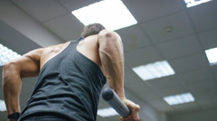 Young male doing tricep dips in a gym Stock Footage