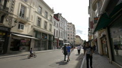 Boy riding a bike while other people are walking on Midi Street in Brussels Stock Footage