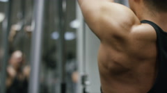 Muscular weight lifter finishing his set of lateral pulldowns Stock Footage