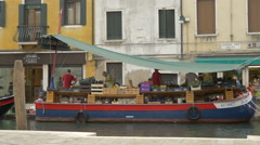 Boat with vegetables and fruits floating on Rio de S. Barnaba, Venice Stock Footage