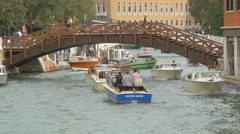 Boats passing under a bridge with wooden railings in Venice Stock Footage