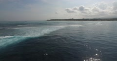 AERIAL slow tilt down following the waves break along the coral reef in Bali Stock Footage