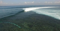 AERIAL static shot of waves breaking over coral reef in Indonesia Stock Footage