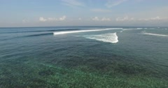AERIAL static shot of clear water and waves breaking near coral reef in Bali Stock Footage