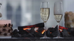 Champagne Pouring from the bottle. Two Flutes with Sparkling Wine over Holiday - stock footage