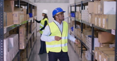 4K Worker in industrial warehouse, listening to music and dancing as he works Stock Footage
