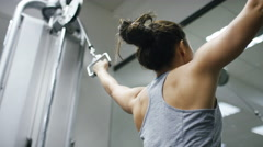 Young woman using a cable pulley machine in the gym Stock Footage