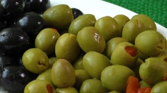 Green and black olives on a white plate Stock Footage