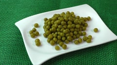Green peas on a white plate - stock footage