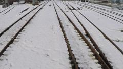 Low altitude motion aerial shot of several railway tracks and switches in snow Stock Footage