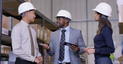 4K Mixed ethnicity management team in industrial warehouse shake hands on a deal - stock footage