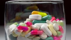 Glass full of medicine : pills, tablets, capsuls, vitamins - zoom out 1 Stock Footage