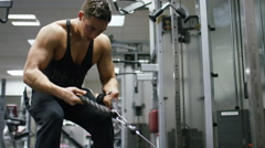 Young man working out in the gym, pulling weights with rope handles Stock Footage