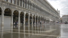 People walking in St Mark's Square during floods in Venice Stock Footage