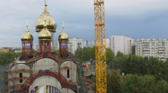 Crane with bell on construction site of church at autumn Stock Footage