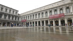 Walking in front of Museo Correr in St Mark's Square during floods, Venice Stock Footage