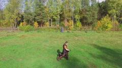 Man trains doberman to walk near master at autumn sunny day Stock Footage