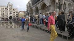 People walking on wooden walkways in Piazza San Marco, Venice Stock Footage