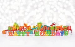 Happy holidays colorful text on the background of gifts - stock photo