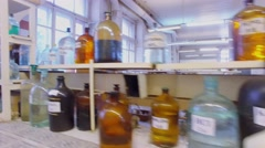 Bottles with many different reagents on desk and shelves - stock footage
