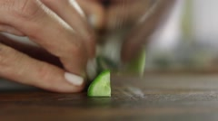 Chef cutting cucumber with shallow depth of field - stock footage