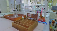 Desk and shelves with many different reagents in bottles - stock footage