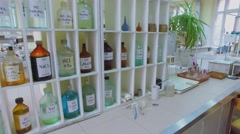 Many different reagents in bottles and vials on desk and shelves - stock footage